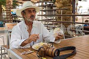 Мужчина в шляпе с фотоаппаратом в кафе