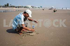 Рыбак ловит в песке червяки для ловли рыбы