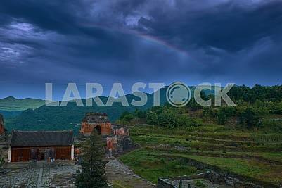Радуга над старинными развалинами храма кунгфу на вершине гор.
