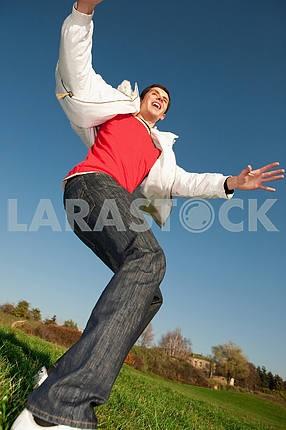 Счастливый молодой человек летит в синем небе