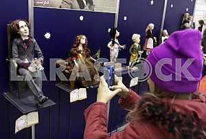 Девочка фотографирует на мобильный телефон куклы на стенде