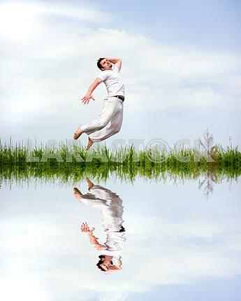 Счастливый человек в белой одежде прыгает по траве возле Лос-Анджелесе