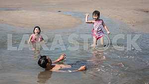 Две девочки и папа купаются на мелководье