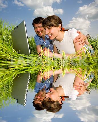 Счастливая пара на ноутбуке на открытом воздухе. Положите на зеленом гра