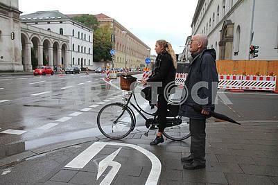 Девушка на велосипеде и мужчина с зонтом