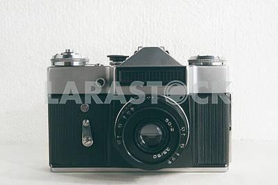 Старый советский пленочный фотоаппарат с объективом на белом фоне крупным планом