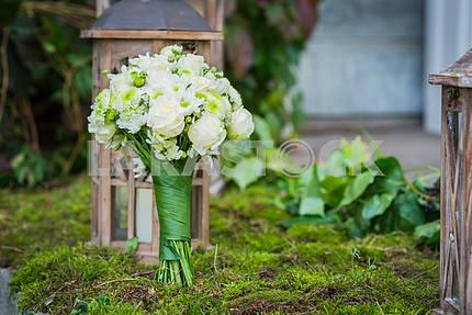 Свадебный букет для невесты из белых роз и зеленых хризантем Старинные деревянные фонарь и мох на заднем плане
