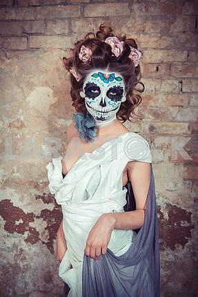 Привлекательная молодая женщина с сахаром череп макияж. Красивая женщина в макияж традиционный мексиканский Calavera черепа Катрины, стоя возле старой кирпичной стены с розами в волосах