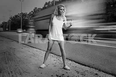 Девушка в светлом платье ловит машину