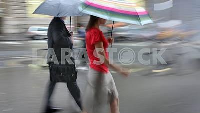 Мужчина и женщина с зонтиками, идущими по улице