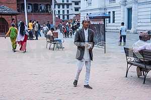 Мужчина в национальной одежде идет по улице.