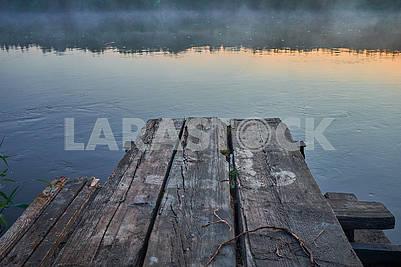 Старая деревянная кладка на реке в туманном рассвете