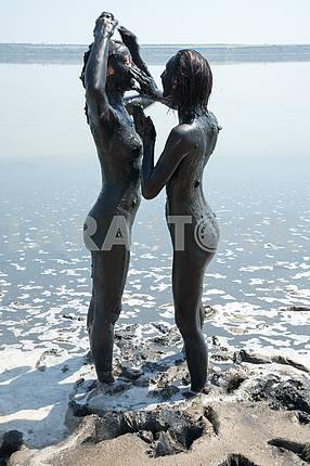 Девушки растирают грязью тело друг друга стоя.