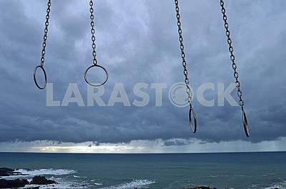 Кільця гімнастичні на пляжі на тлі грозового неба
