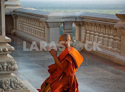 Монах на коленях у храма