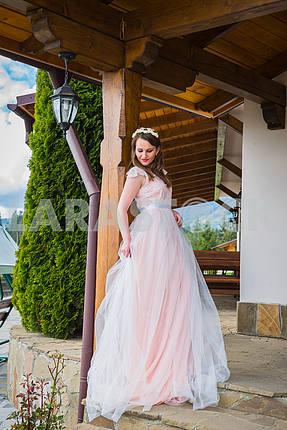 Красивая невеста в длинном платье стоит в дверях и смотрит на улицу. Тюль платье Милая девушка