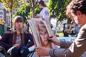 Художник на улице рисует портрет девушки