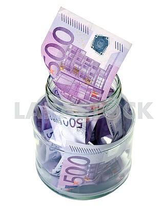 Евро в стеклянной банке на белом фоне