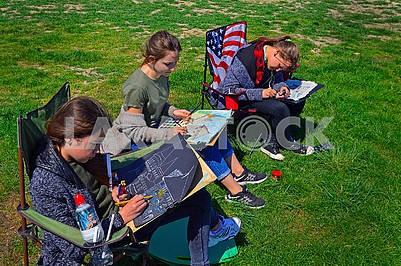 Три молоді дівчини малюють