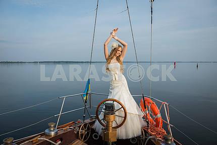 Свадьба на парусной яхте. Счастливая невеста возле рулевого колеса, красивая блондинка в свадебное платье. голубое небо