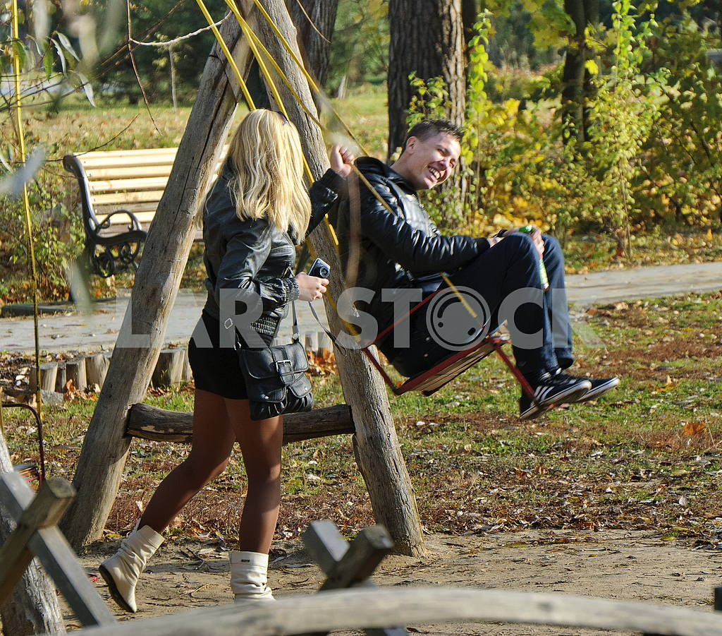 Boy and girl go for a drive on a swing in the park Kiev Feofania — Image 34310