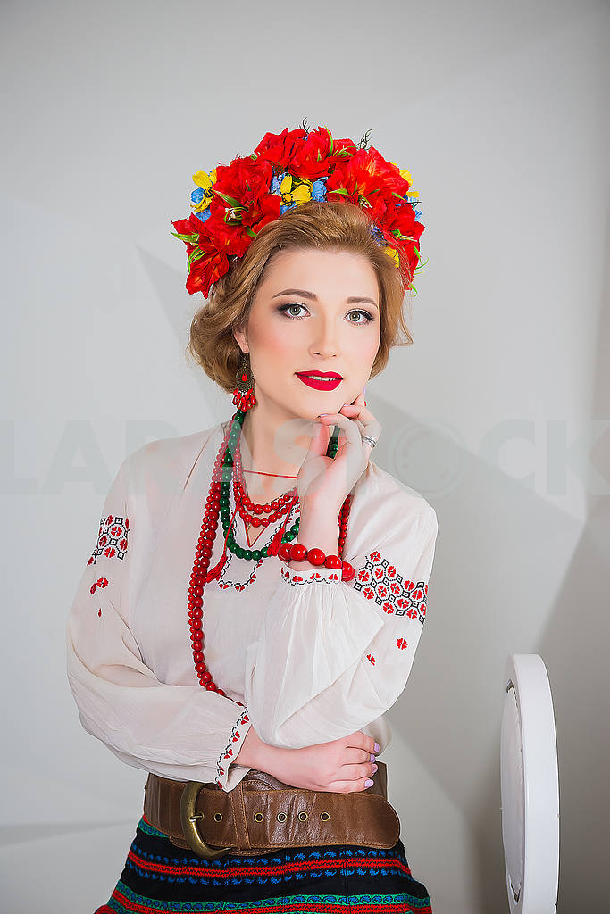 A beautiful girl in National Ukrainian Costume. captured in studio. Embroidery and jacket. wreath. circlet of flowers. red lips — Image 54310