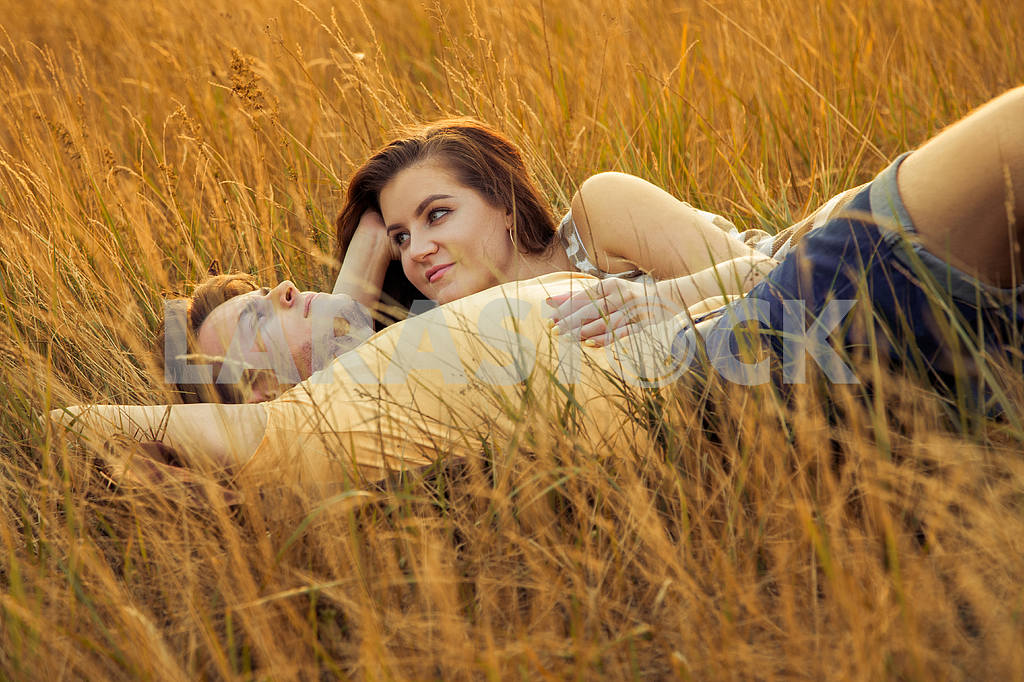 Young fashion beautiful loving casual style couple  lying down on floral field in autumnal park, warm sunny day, enjoying family, romantic date, happiness and love concept. — Image 19840