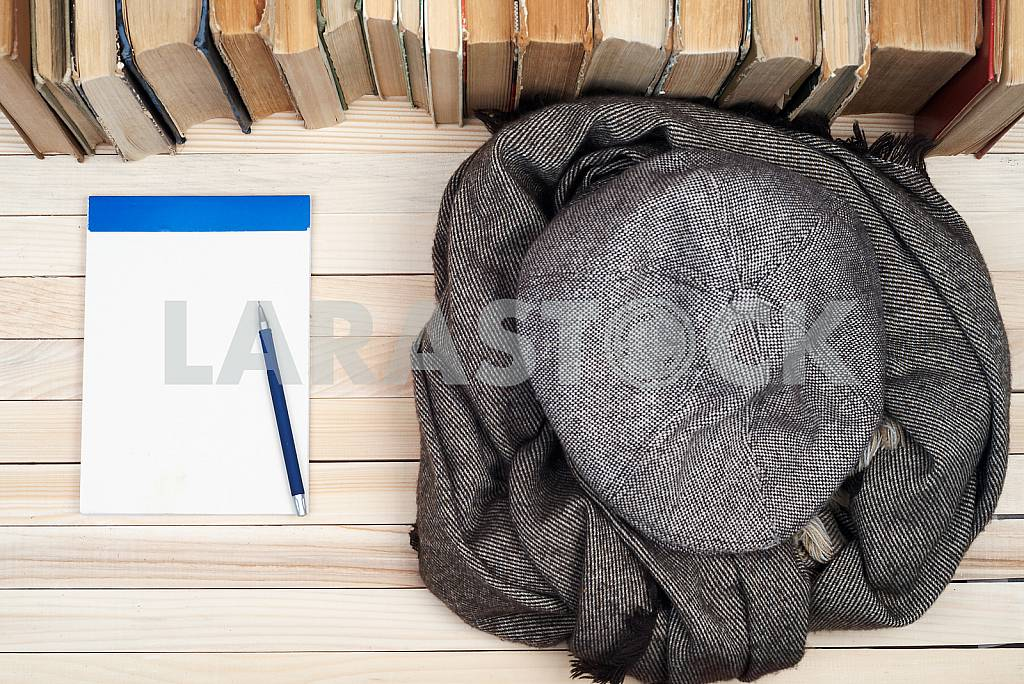 On a wooden table books, documents, calculator, red briefcase. — Image 39850