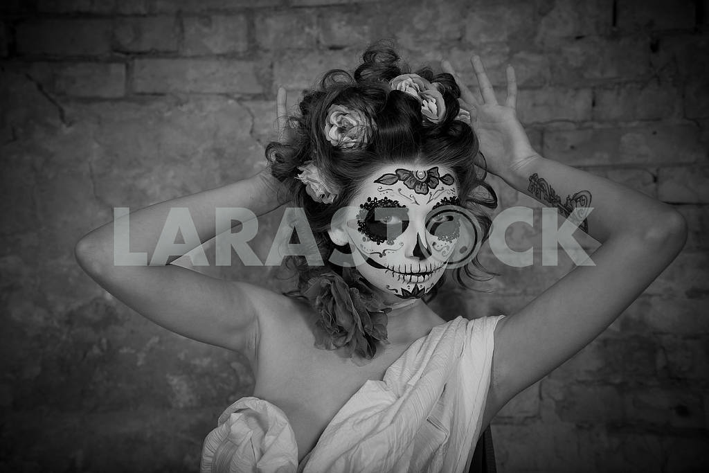 Attractive young woman with sugar skull makeup. Beautiful woman in makeup traditional Mexican Calavera skull Katrina, standing near the old brick wall  with the roses in her hair - black and white — Image 38560