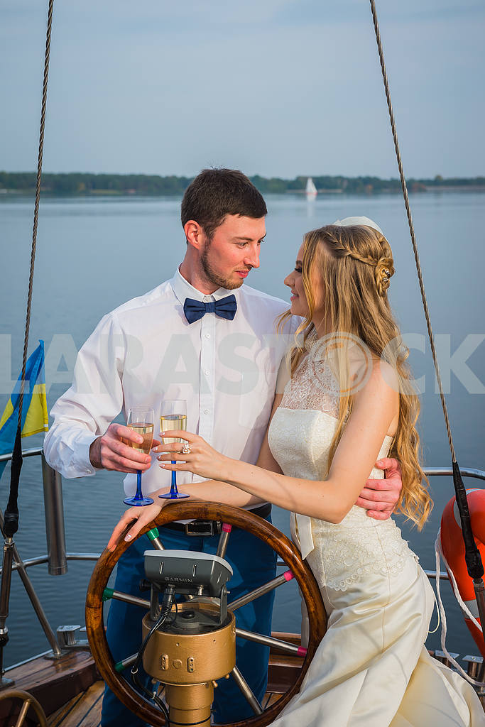 Happy bride and groom hugging on a sailing yacht with the champagne  in their hands on a sunny day; stylish, long dress, bow tie — Image 46070