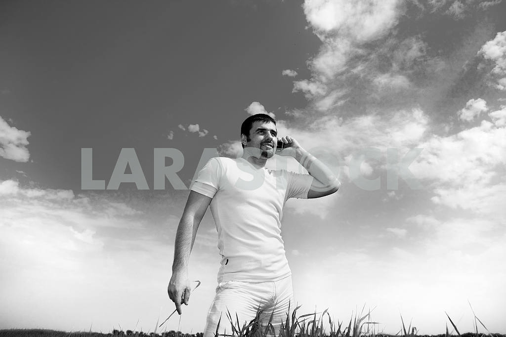 Man at the phone in the field. In white dress — Image 6270