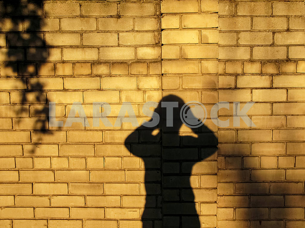 Shadow of a man, who holding on behind his head. — Image 82701