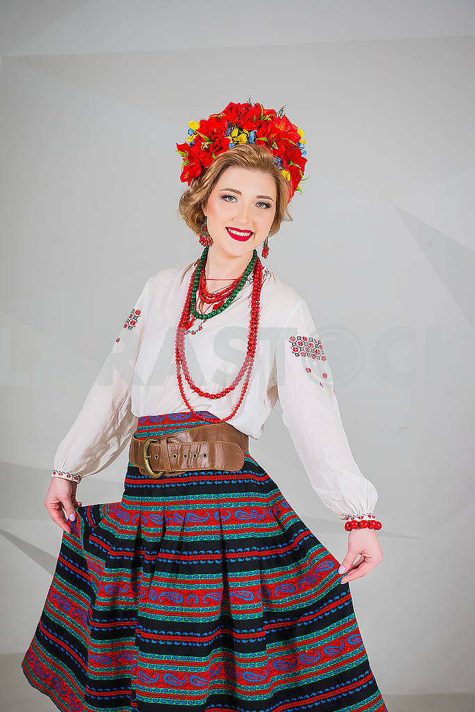A beautiful girl in National Ukrainian Costume. captured in studio. Embroidery and jacket. wreath. circlet of flowers. red lips — Image 54311