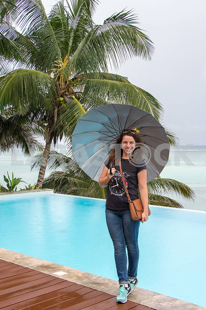 Girl standing with umbrella in hand on background of ocean — Image 32031