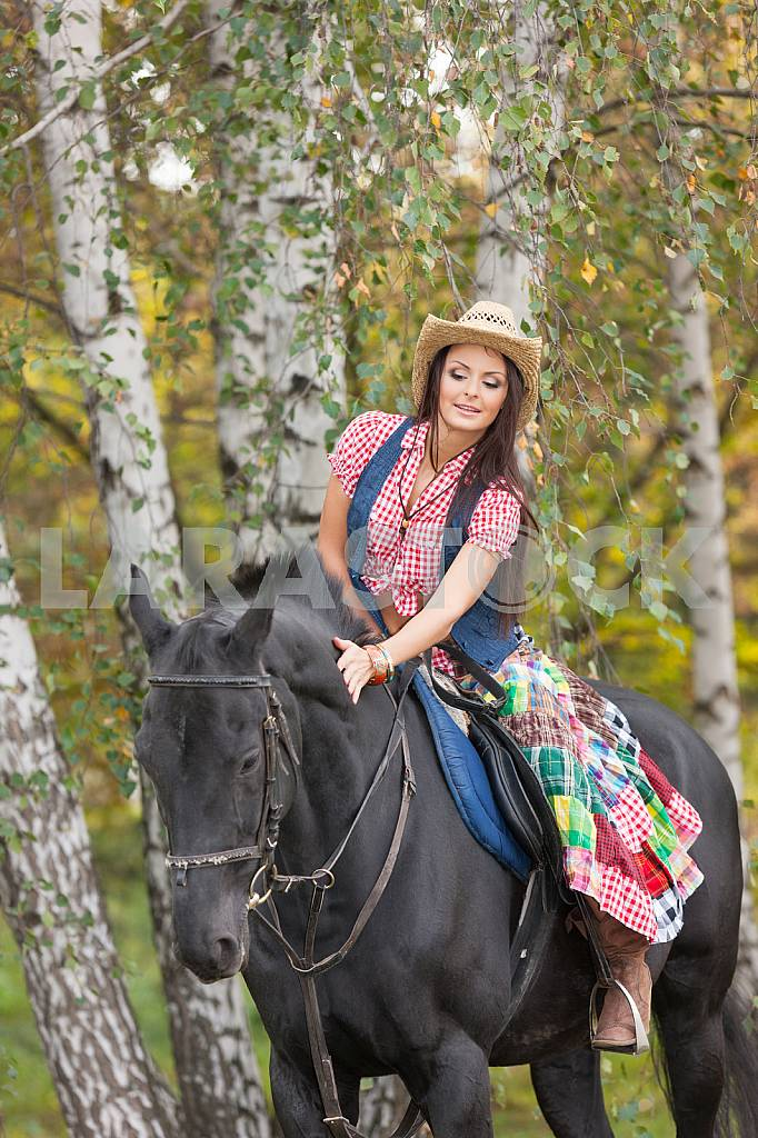 Beautiful smiling woman caress black horse — Image 22542