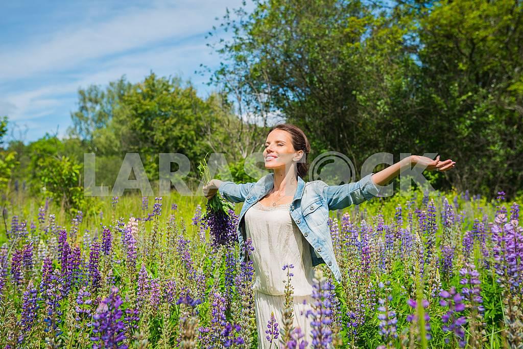 Молодая женщина, брюнетка, счастливым, стоя среди поля фиолетовыми люпина, улыбаясь, фиолетовые цветы. Голубое небо на заднем плане. Лето, солнечный день! — Изображение 31252