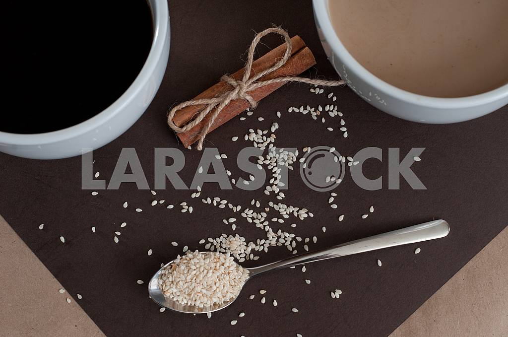 Black coffee and coffee with milk in white cups. Cinnamon and sesame. — Image 32772