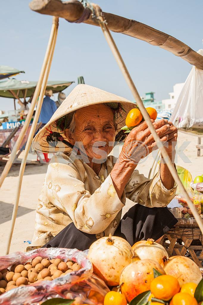 Grandmother, a saleswoman of fruit sitting near the basket — Image 28192