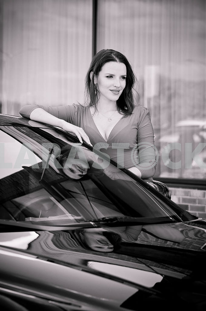 Beautiful brunette standing near the car, her reflection in the glass, looking to the right, black and white — Image 38203