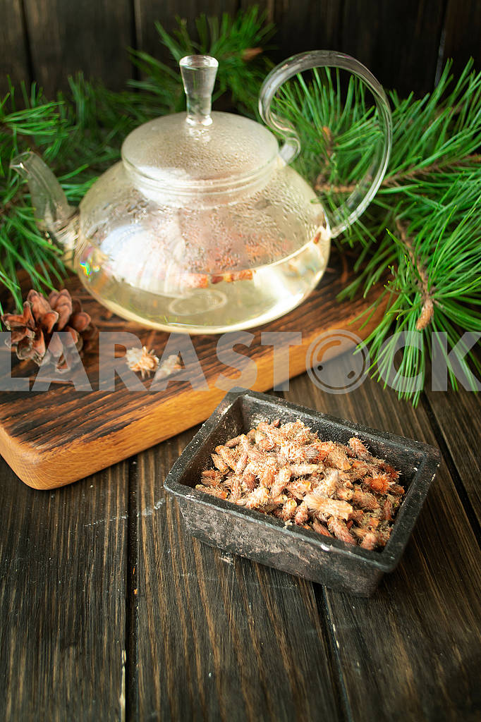 Tea pot of herbal tea with pine buds on wooden background — Image 83023