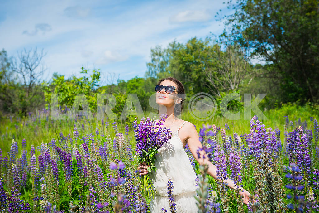 Young woman, happy, standing among the field of violet lupines, smiling, purple flowers. Blue sky on the background. Summer, with bouquet, in sunglasses looking in the sky, dreaming — Image 34543