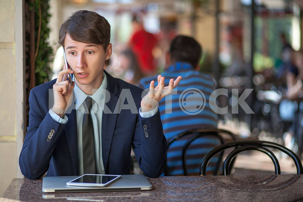 One relaxed young handsome professional businessman working with his laptop, phone and tablet in a noisy cafe. speak with phone. — Image 9543