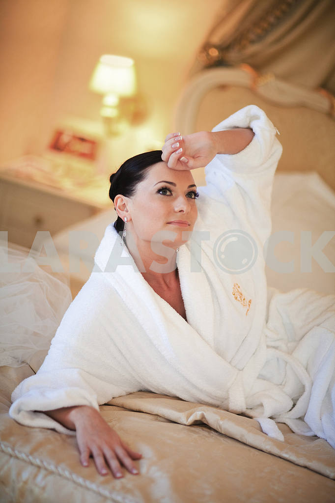 Beautiful girl in a white coat lying on the bed — Image 5963