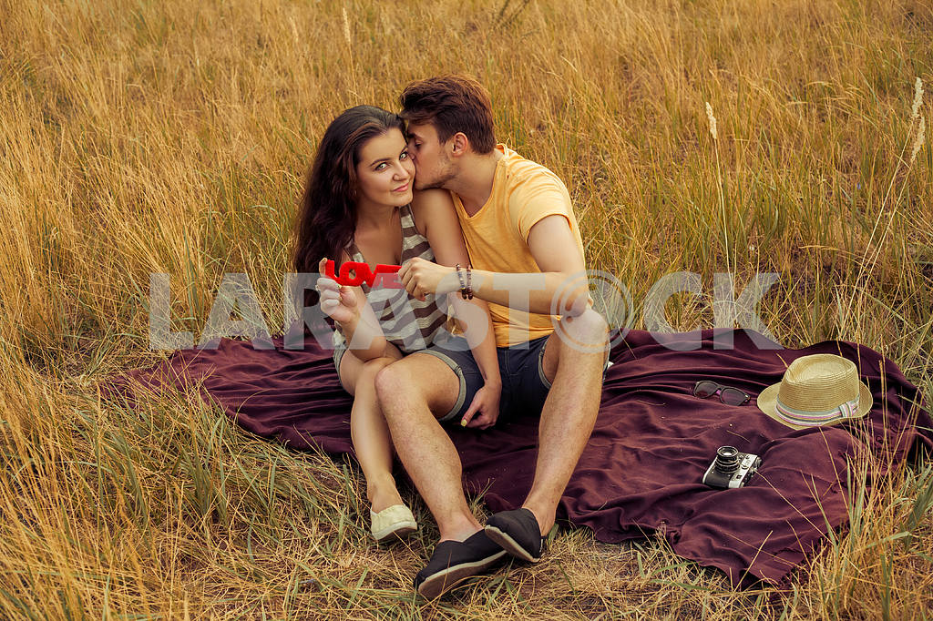 Young fashion beautiful loving casual style couple  lying down on floral field in autumnal park, warm sunny day, enjoying family, romantic date, happiness and love concept. — Image 19873