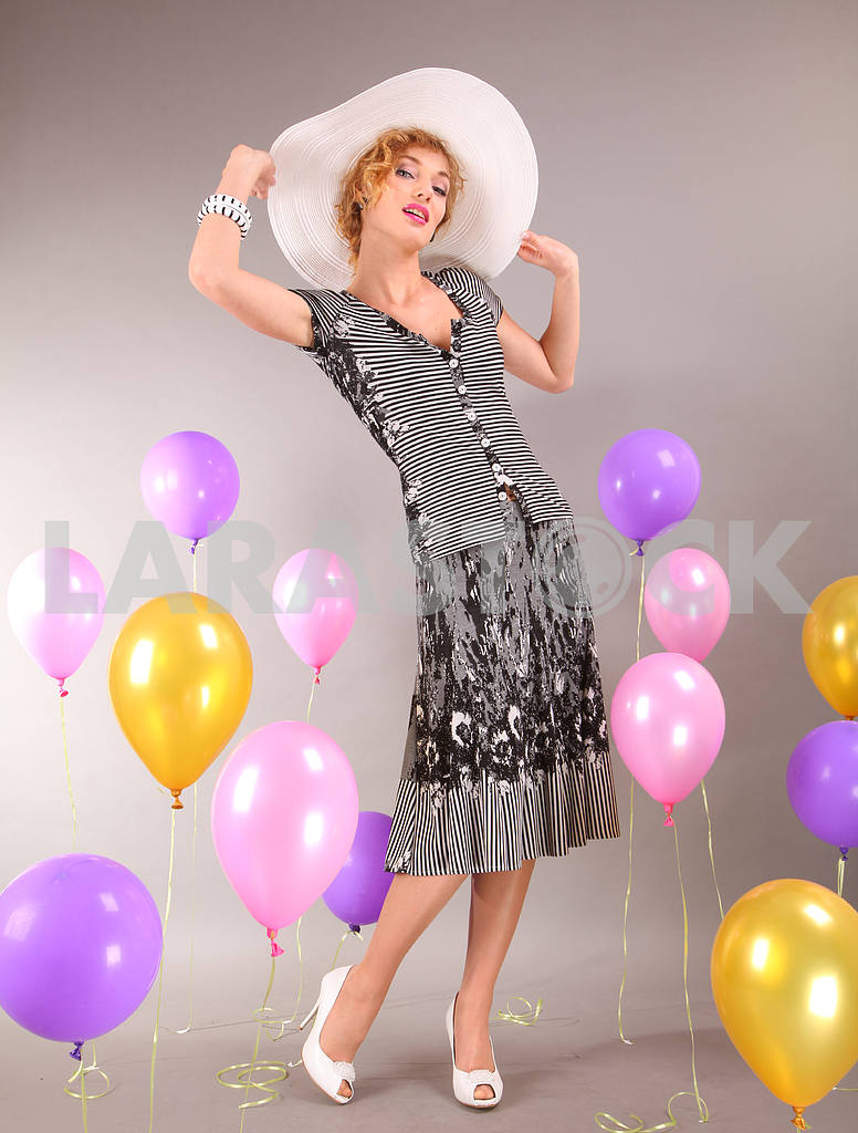 Beautiful young girl in light dress a hat on background balloons — Image 7655