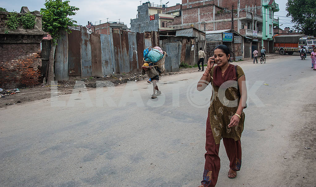 A girl walking down the street, talking on the phone — Image 50565