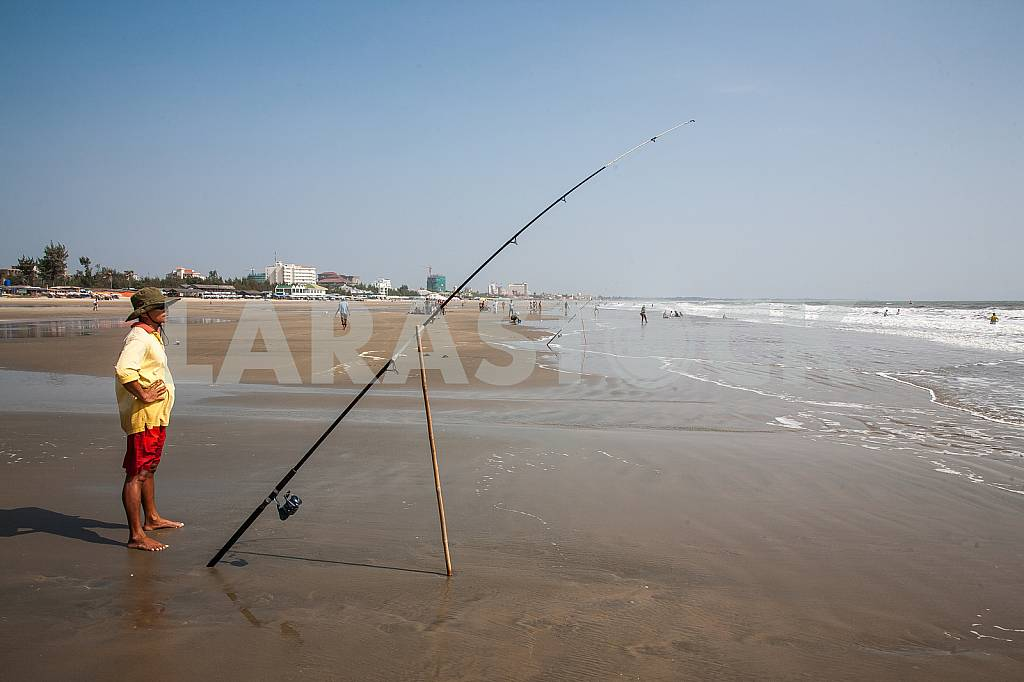 Fisherman with spinning near the sea — Image 28185