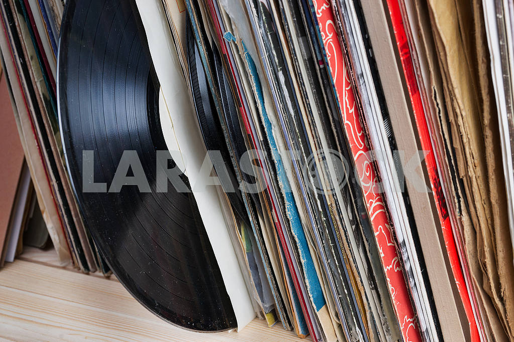 Retro styled image of a collection of old vinyl record lp's with sleeves on a wooden background. Copy space — Image 46806