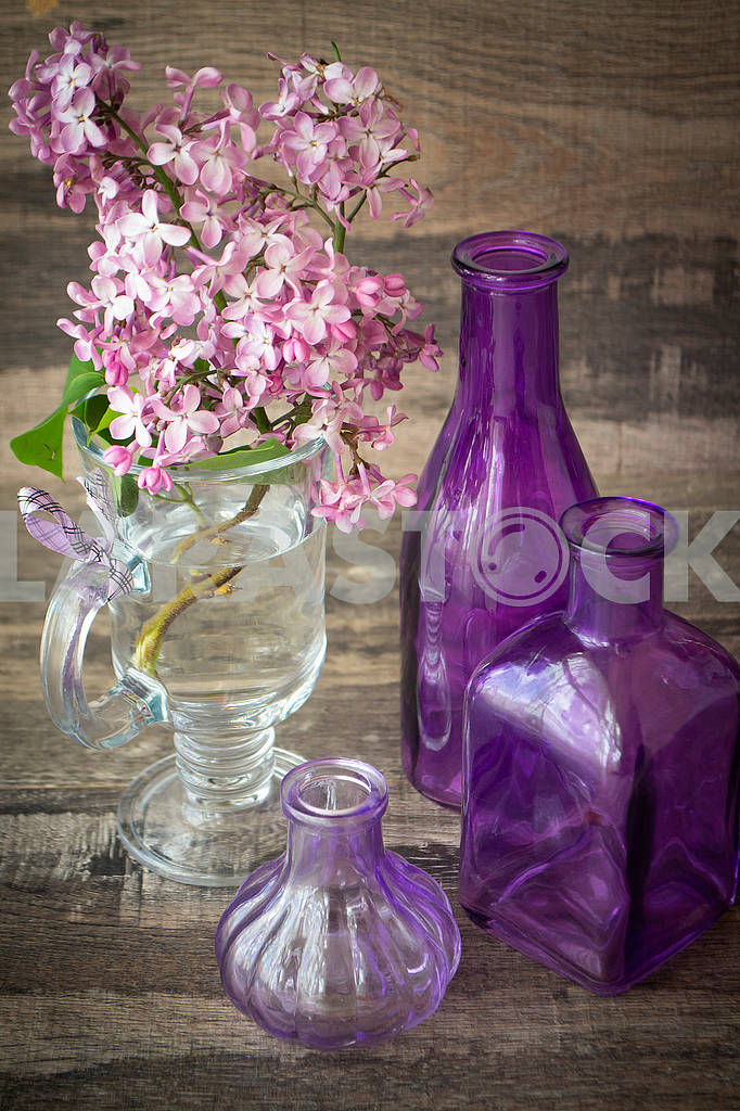 Branch of blooming lilac in a glass bottle with violet bottles decoration — Image 83156