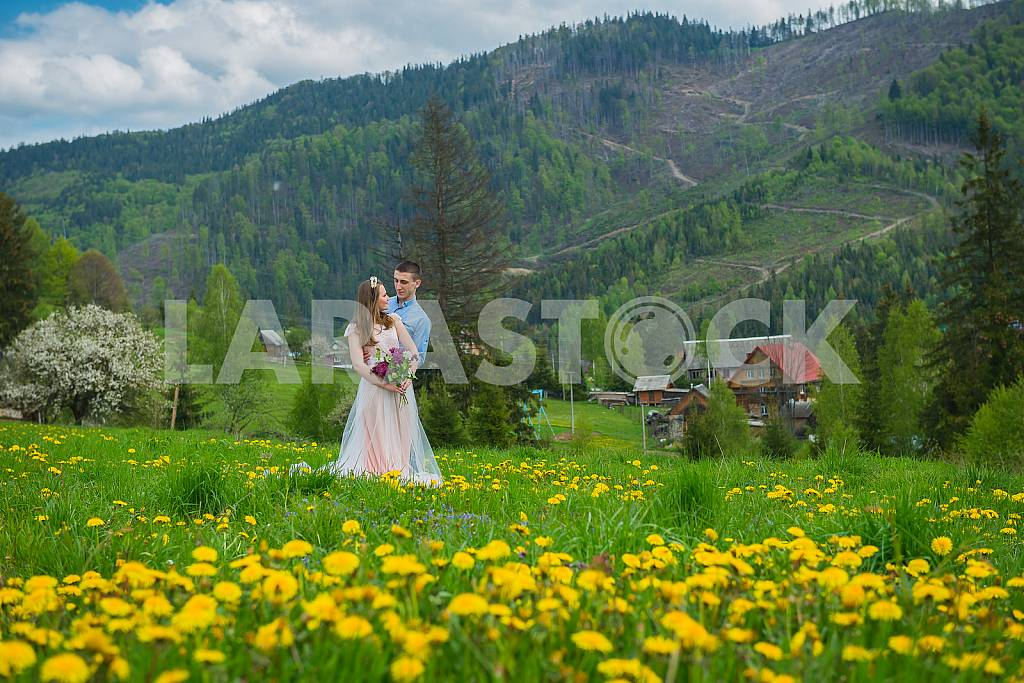 Wedding in mountains, A COUPLE IN LOVE, MOUNTAINS background, STANDING surounded dandelions, AMONG THE LAWN WITH THE GREEN GRASS, RUSTIC STYLE, GIRL IN LONG TULLE DRESS, romantic landscape — Image 30527